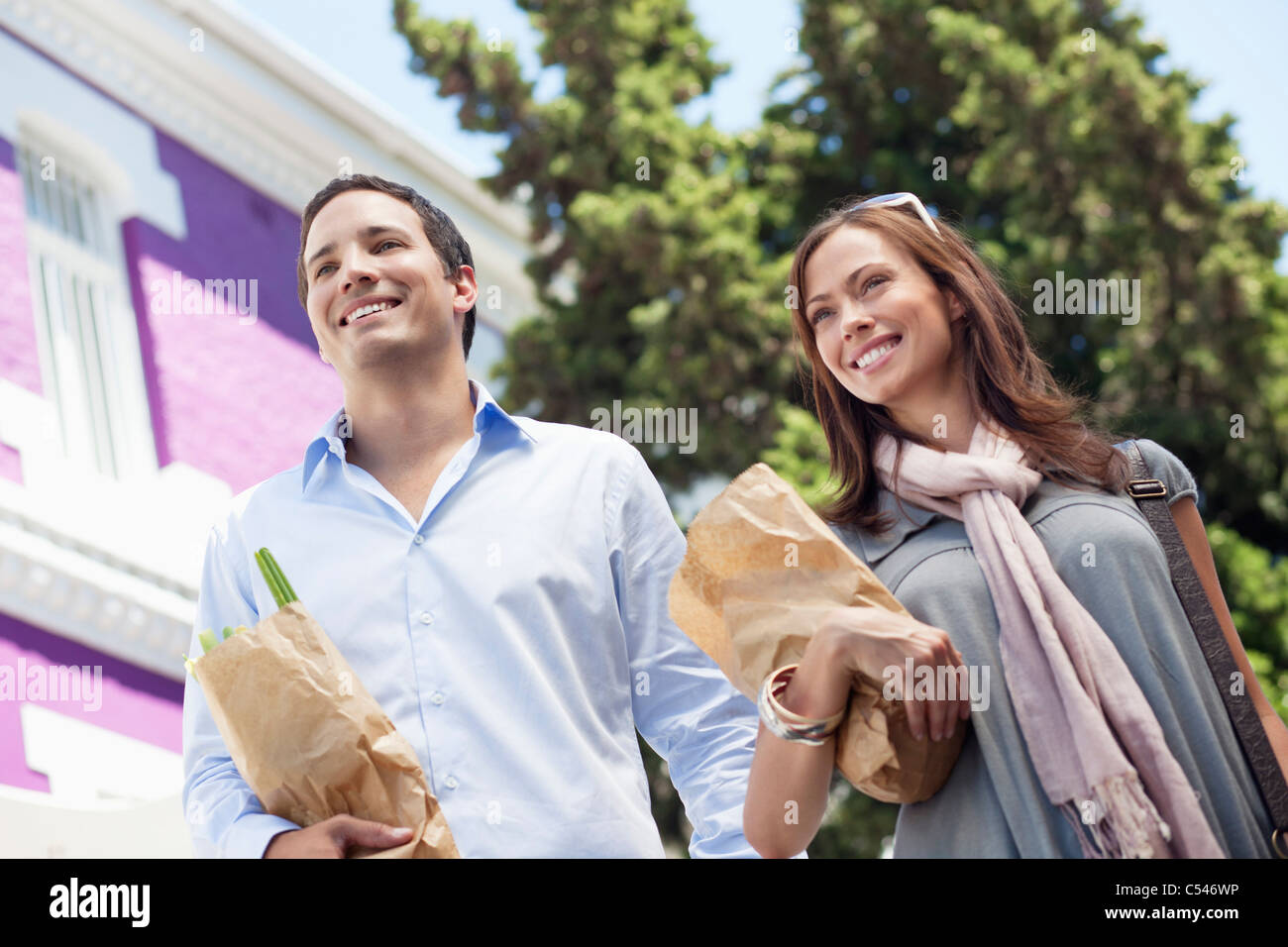 Smiling couple standing with paper bags full of vegetables - Stock Image