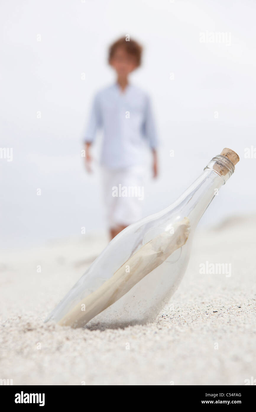 Blurred boy walking towards bottle with note inside on beach - Stock Image