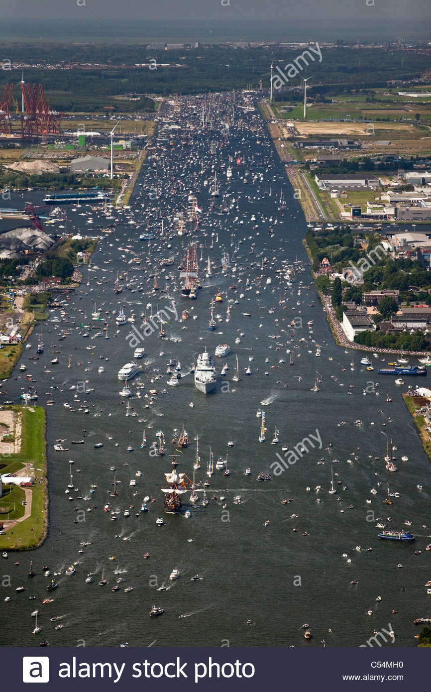 Aerial of parade of tall ships from IJmuiden to Amsterdam through canal called Noordzeekanaal. View on Amsterdam - Stock Image