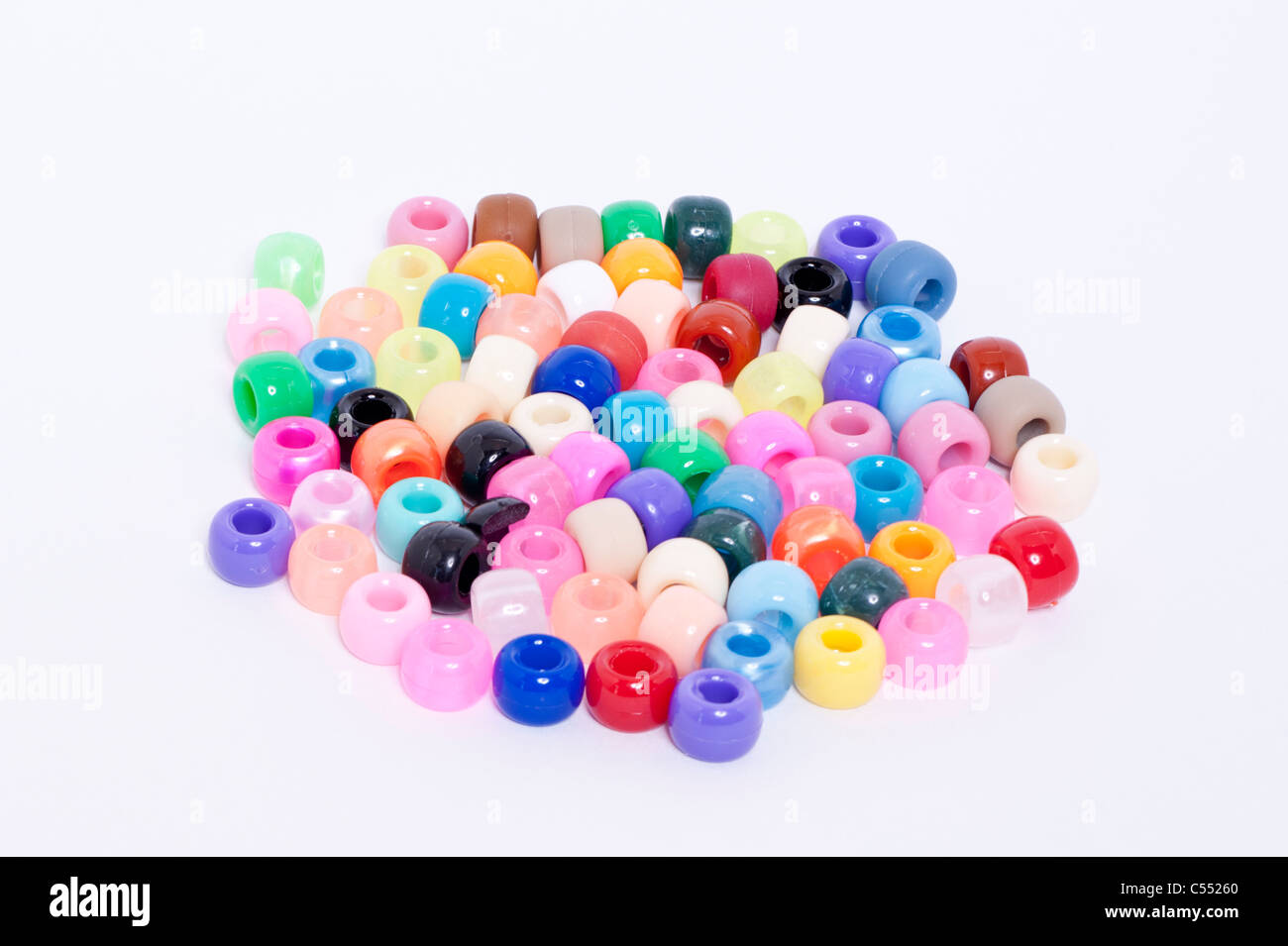 A selection of coloured beads on a white background - Stock Image