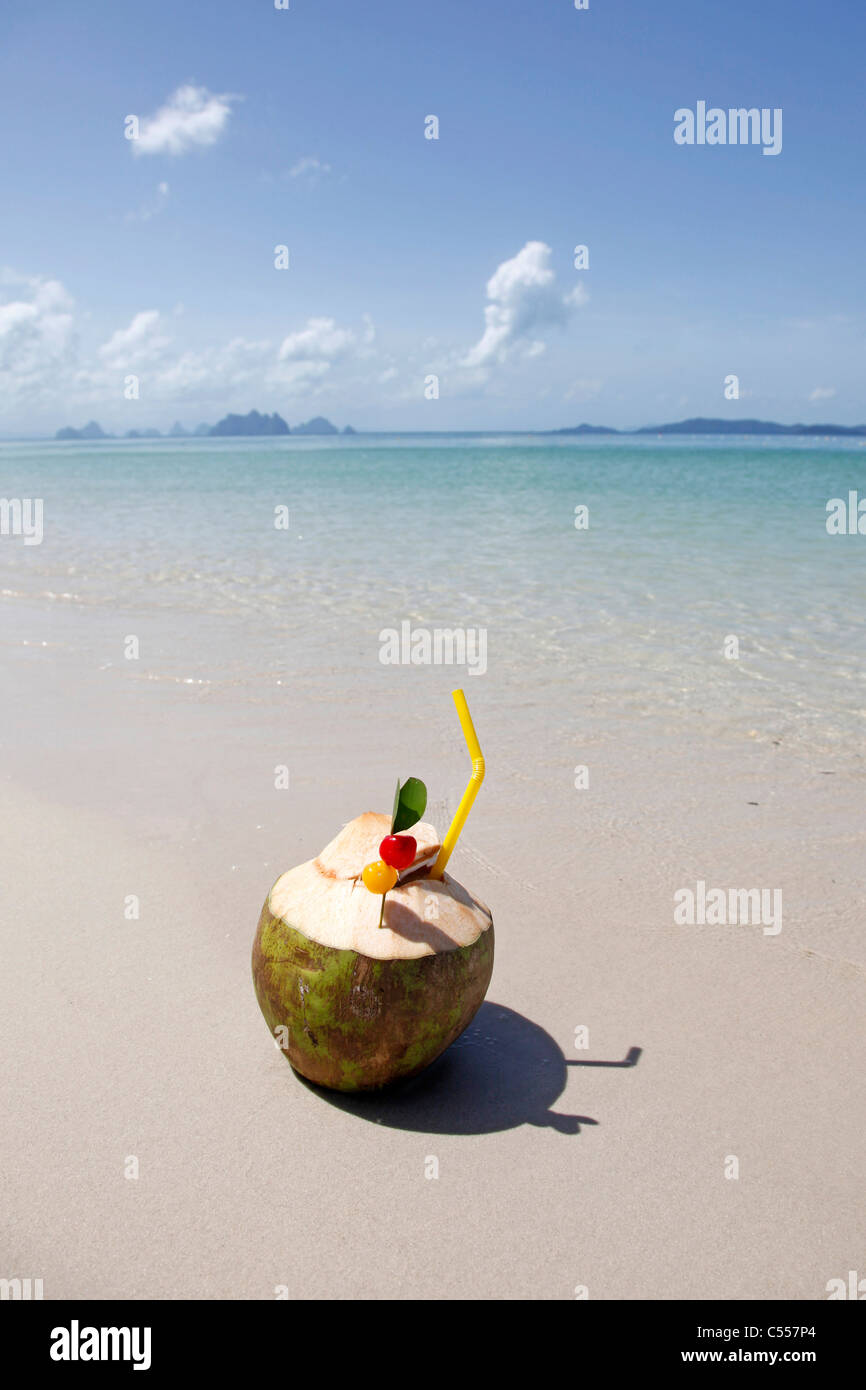 Pina Colada cocktail in a coconut on the beach in Phuket, Thailand - Stock Image