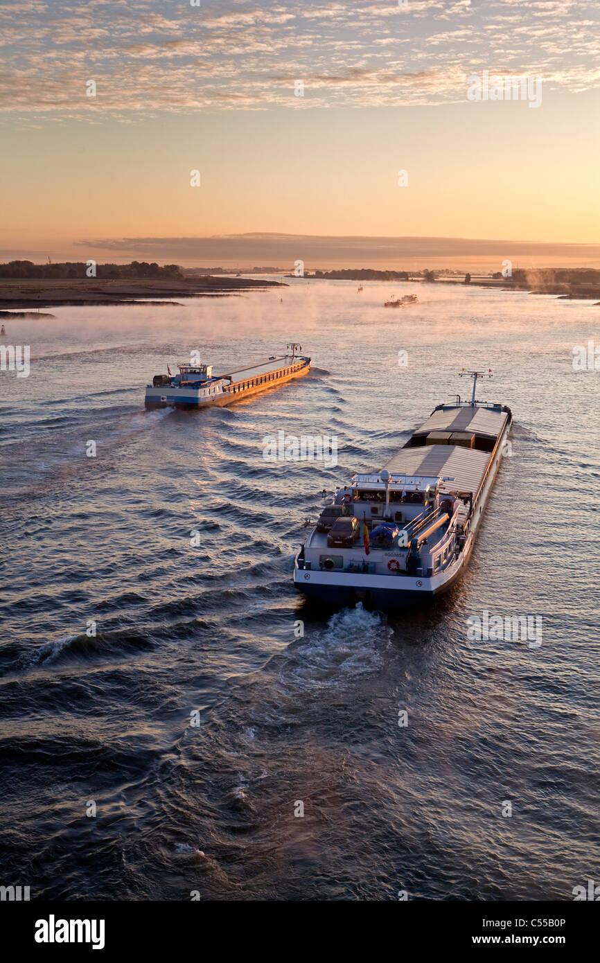 The Netherlands, Nijmegen, Cargo boats on Waal river. Sunrise. - Stock Image