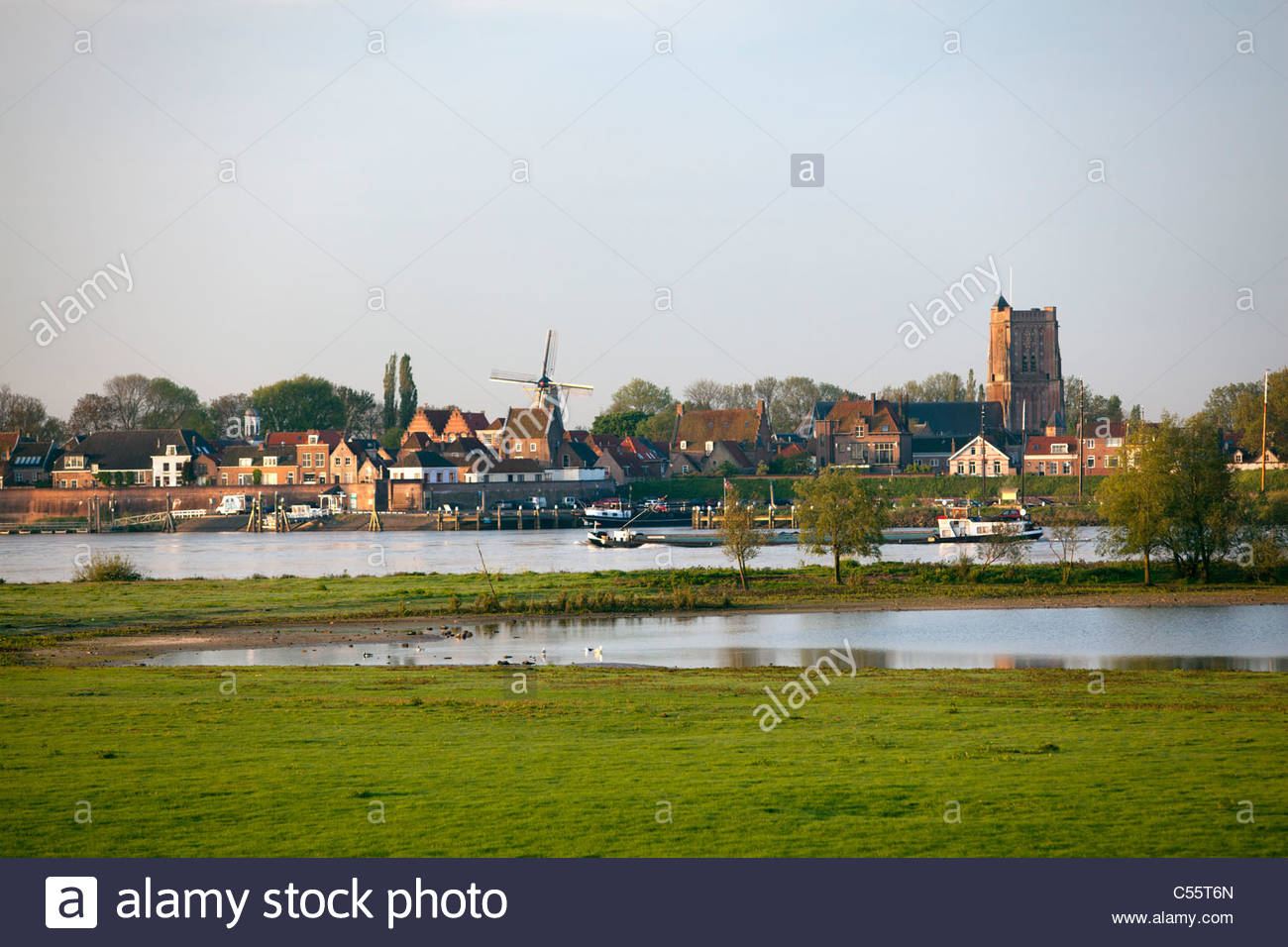 The Netherlands, Woudrichem, Skyline and cargo ship in river called Maas. - Stock Image