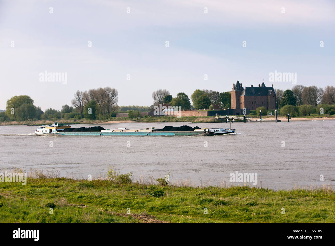 The Netherlands, Woudrichem, Loevestein Castle and cargo ship in river called Maas. - Stock Image