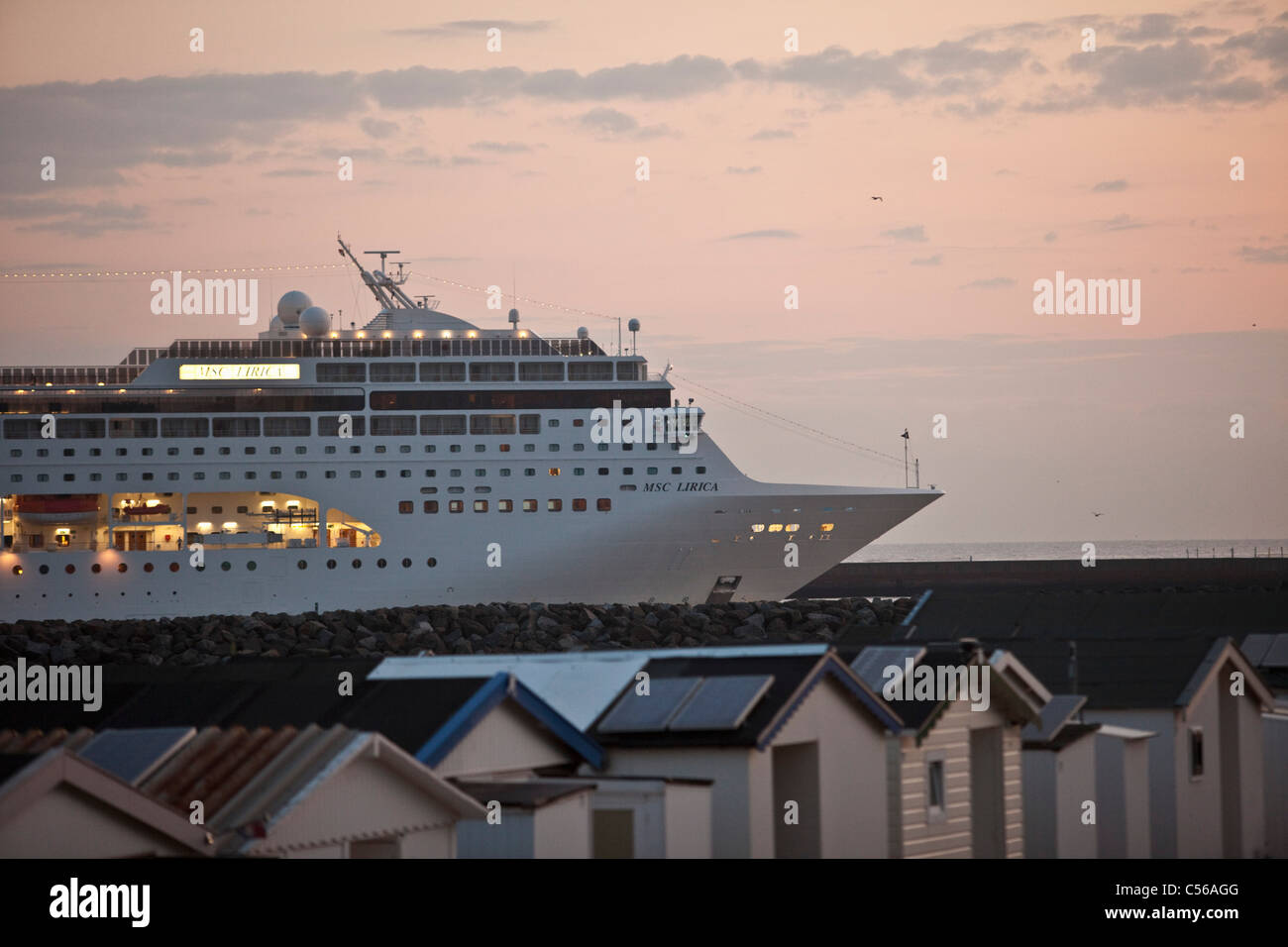 The Netherlands, IJmuiden, Cruise ship arriving at North Sea Canal. Sunrise. Beach cabins. - Stock Image