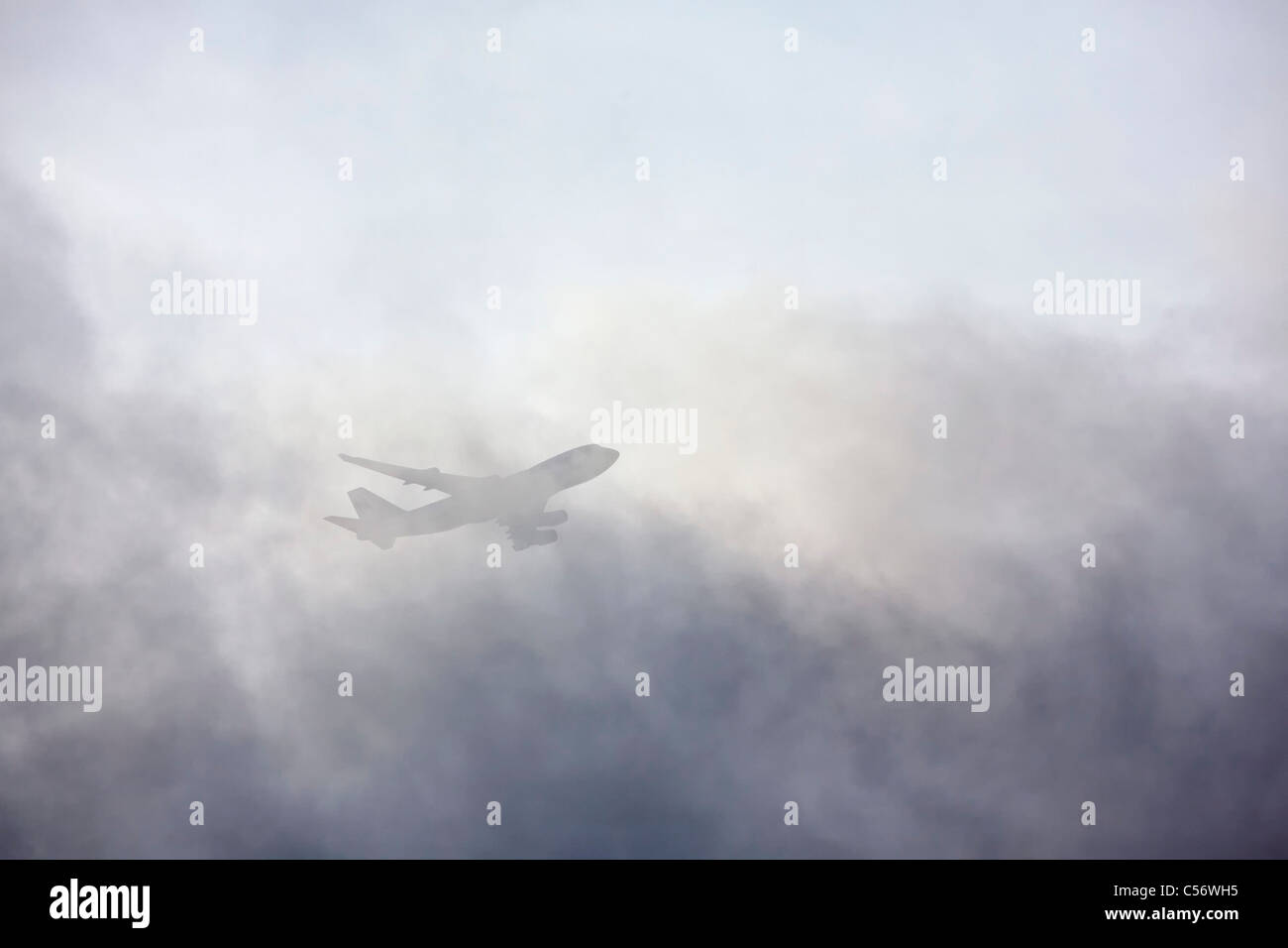 The Netherlands, Weesp, Airplane flying through clouds. - Stock Image