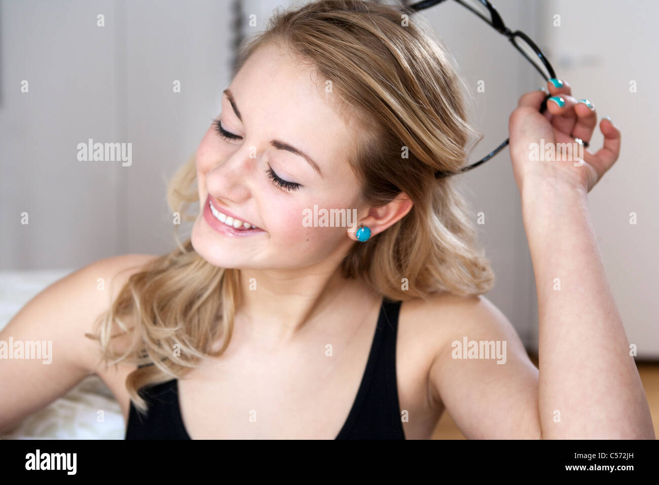 Woman taking off her glasses - Stock Image