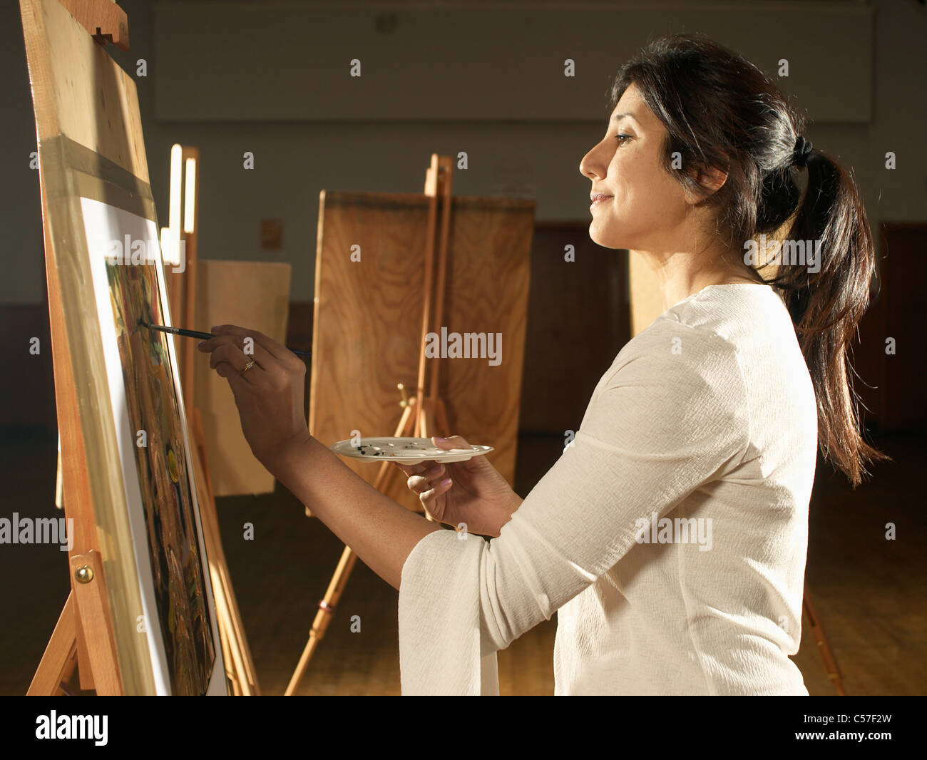 Artist painting in studio - Stock Image