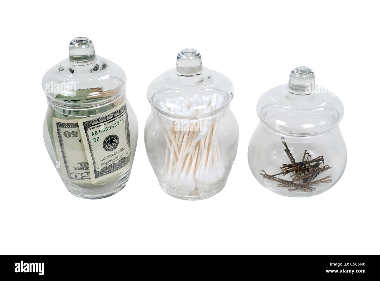 Old glass apothecary jars with fitted lids filled with money, cleaners and hair clips - path included - Stock Image