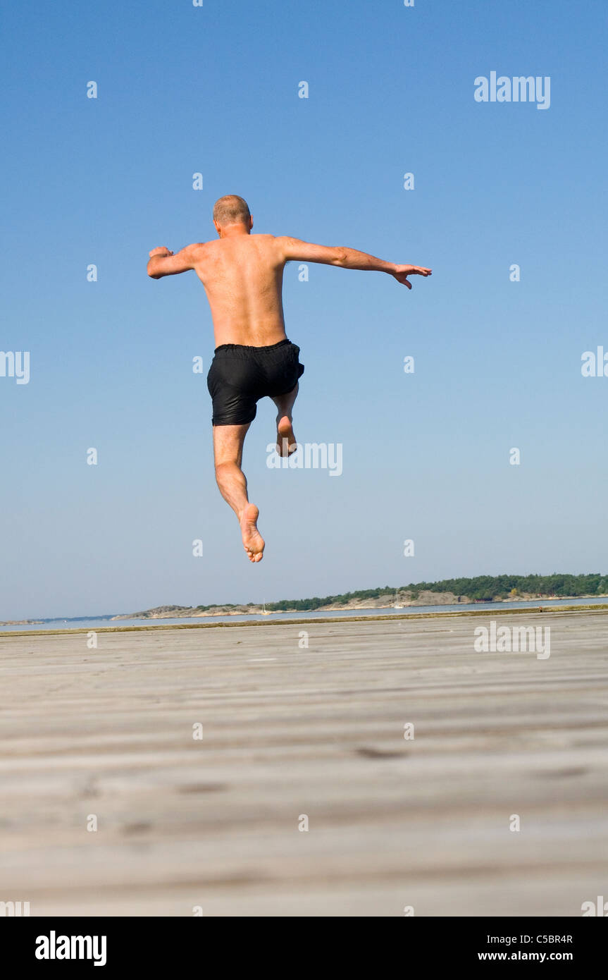 Rear view of a shirtless man jumping on sand against clear blue sky - Stock Image