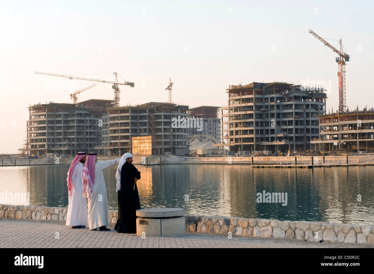 Elk204-1007 Bahrain, Manama, Arab men in traditional dress looking at high rise construction from across harbor - Stock Image