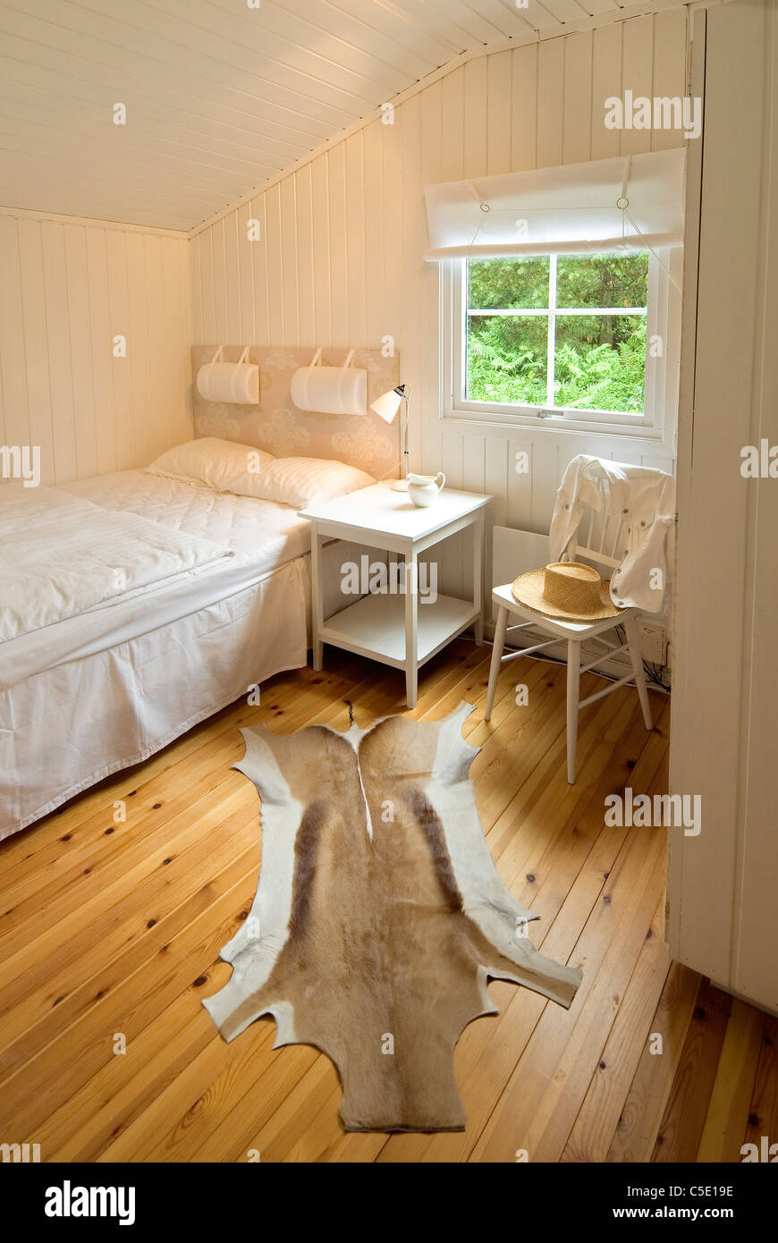 View Of A Window By Bed With Animal Skin Rug On Wooden Floor At A