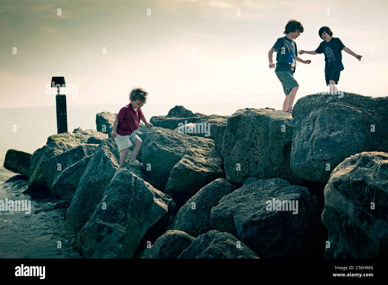 Boys playing on rocks by the sea - Stock Image