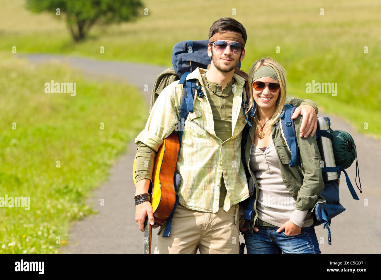 Hiking young couple backpack tramping on asphalt road sunny countryside - Stock Image