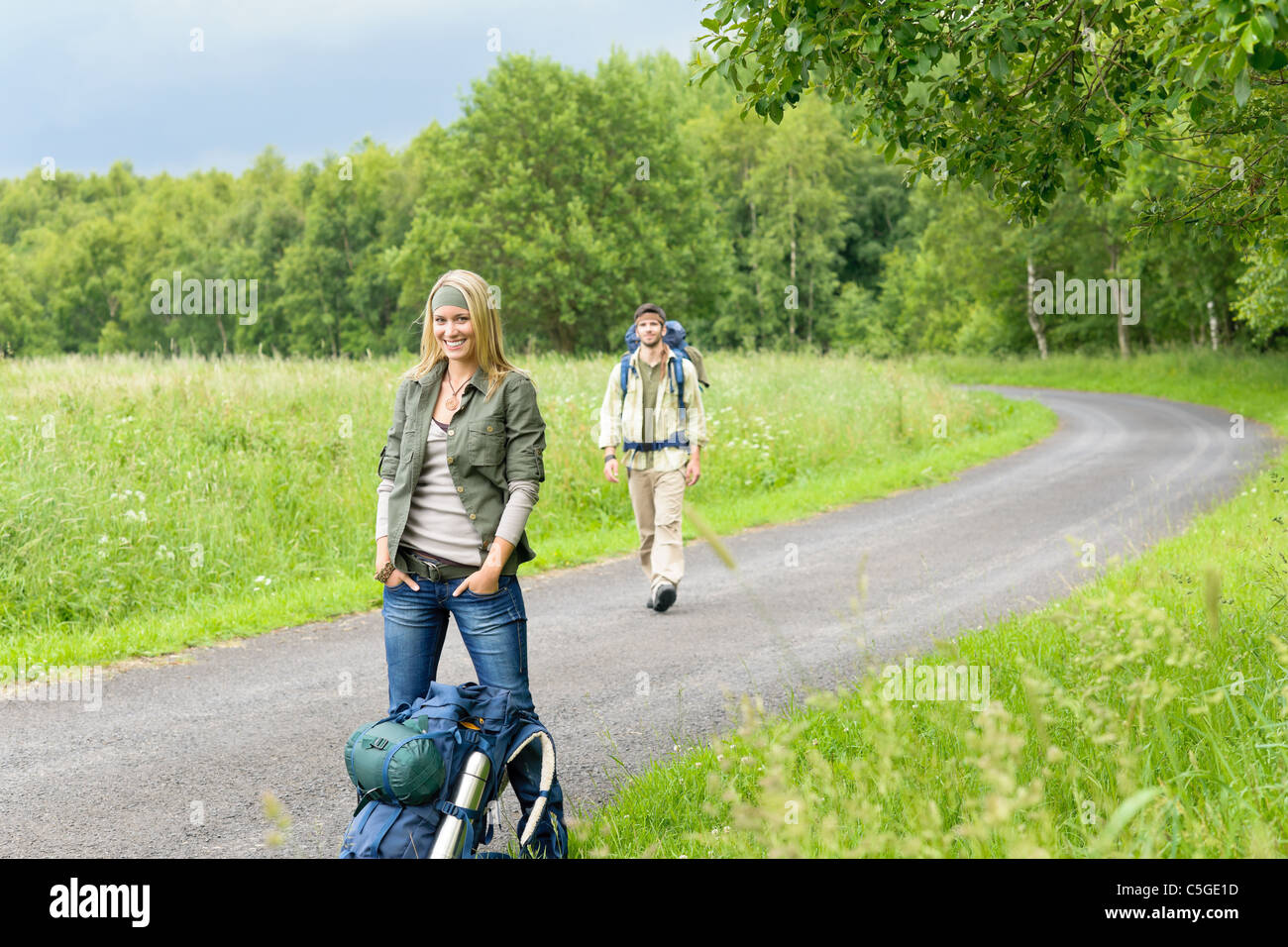 Hiking young couple backpack tramping on asphalt road countryside - Stock Image