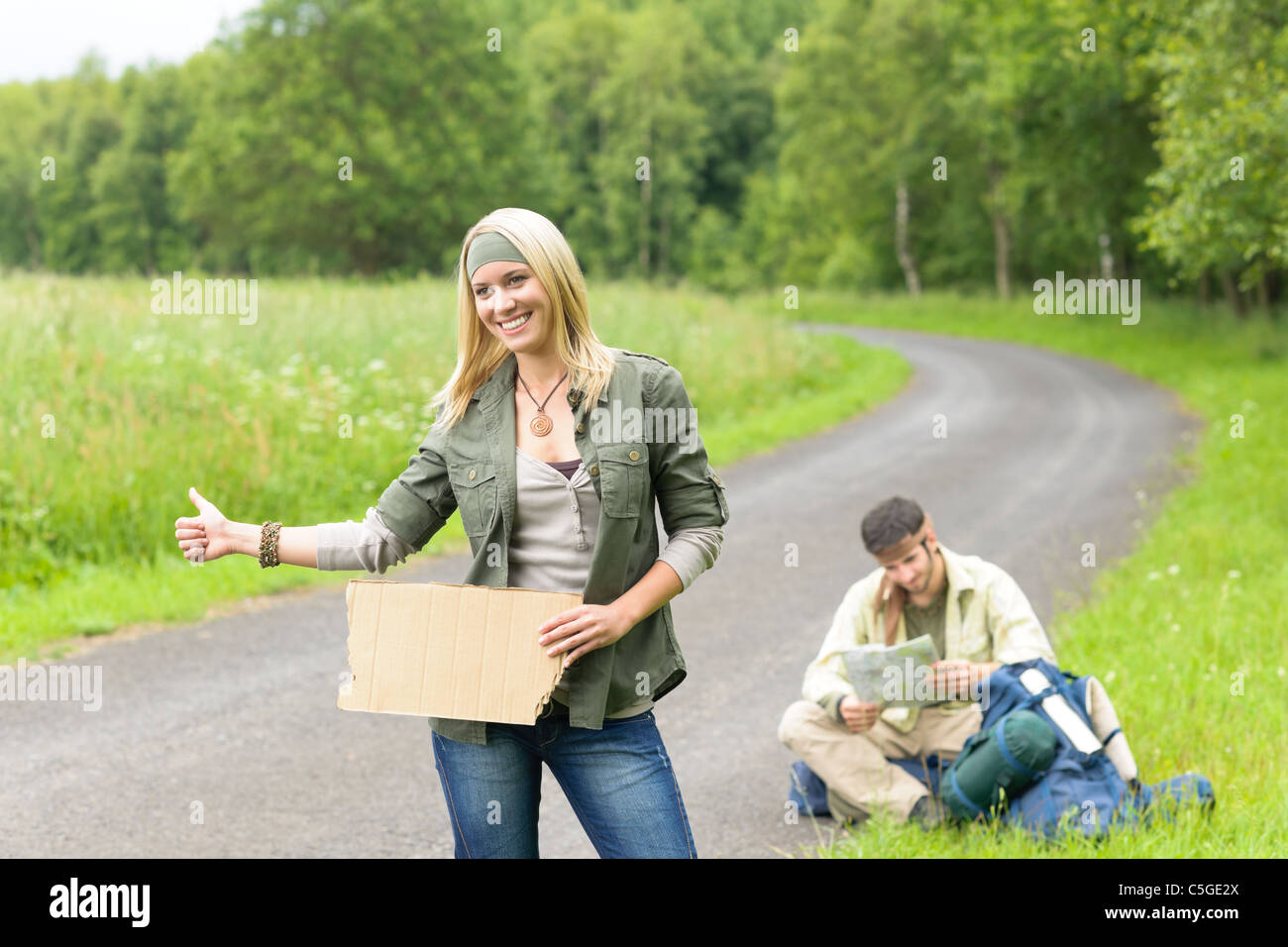 Hitch-hike young couple backpack tramping on asphalt road play guitar - Stock Image