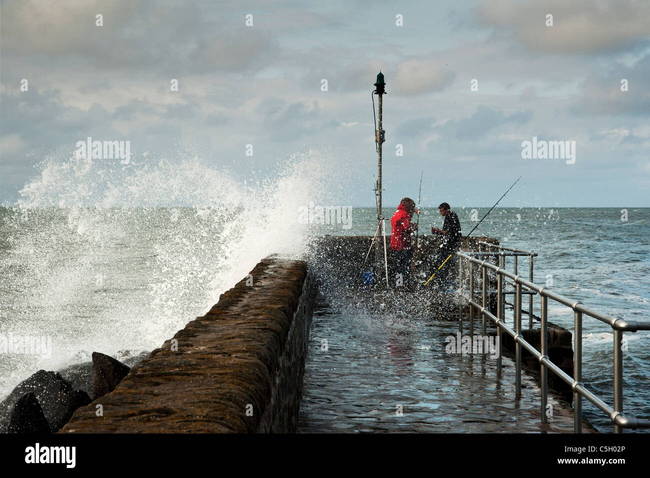Big wave crashes over the sea defenses and splashes two sea fishermen at Lynton on the North Devon Coast, England, - Stock Image