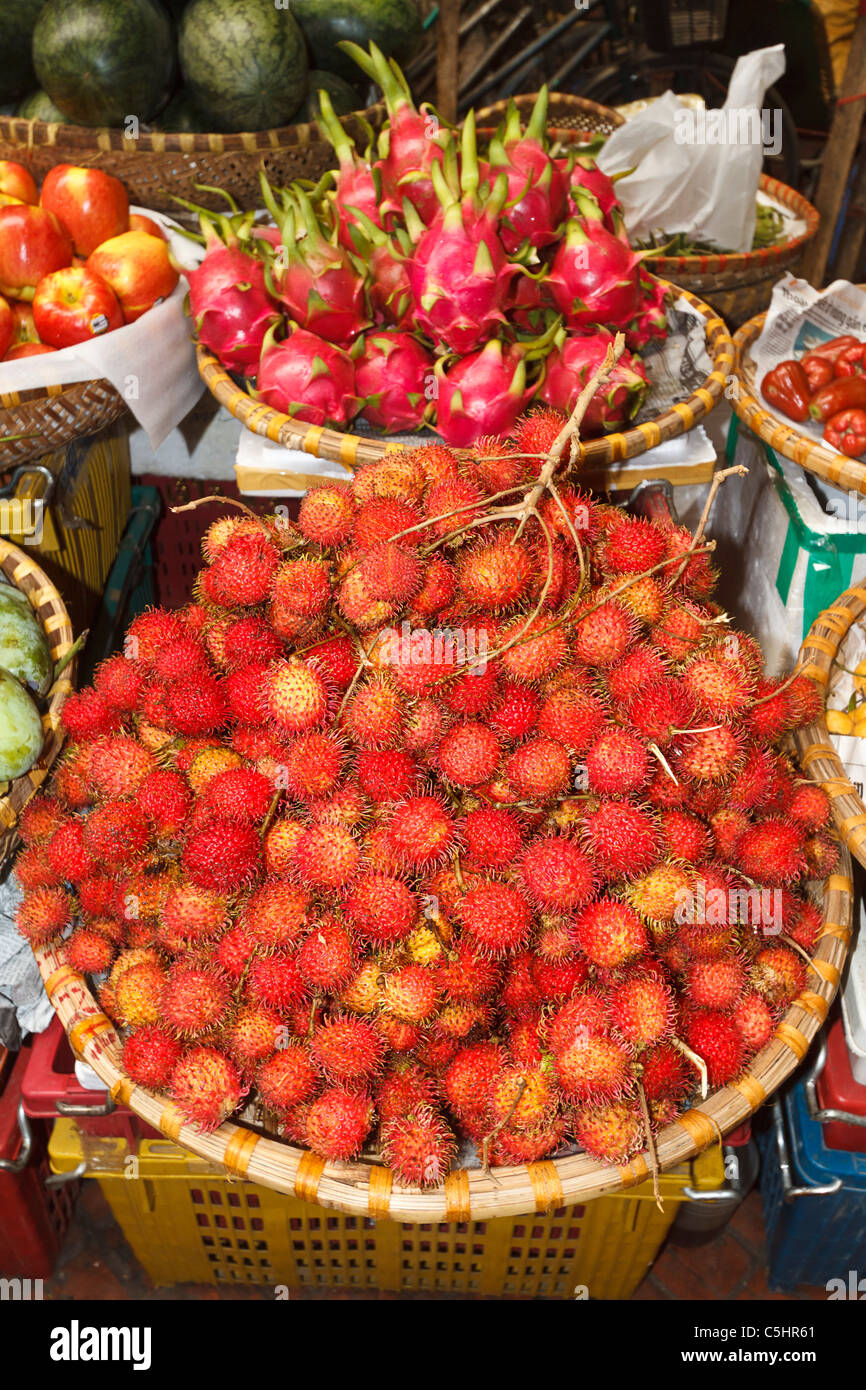 Rambutan, lychee like fruit for sale in Hom Market, a typical crowded market in the Old Quarter of Hanoi - Stock Image