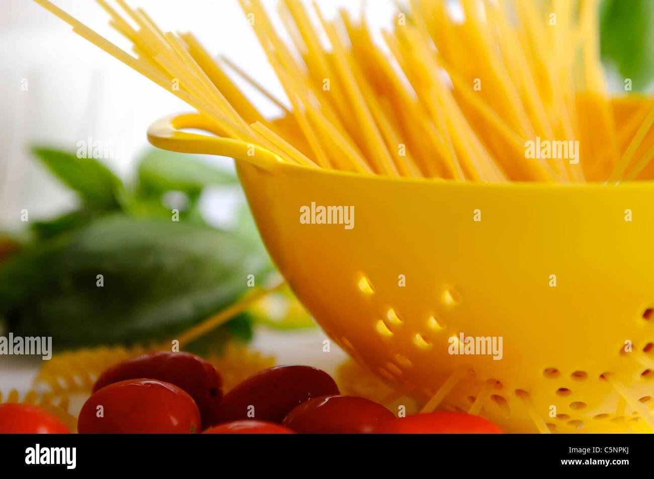 Raw spaghetti in a yellow colander - Stock Image