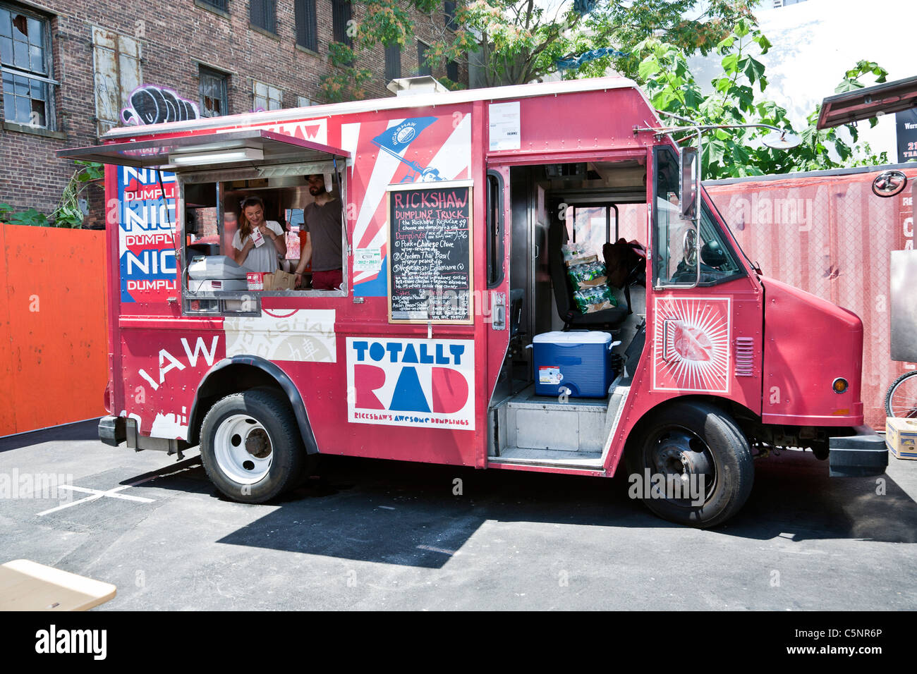 bright pink Thai dumpling food truck parked in lot next to High Line elevated park entrance Chelsea district New - Stock Image