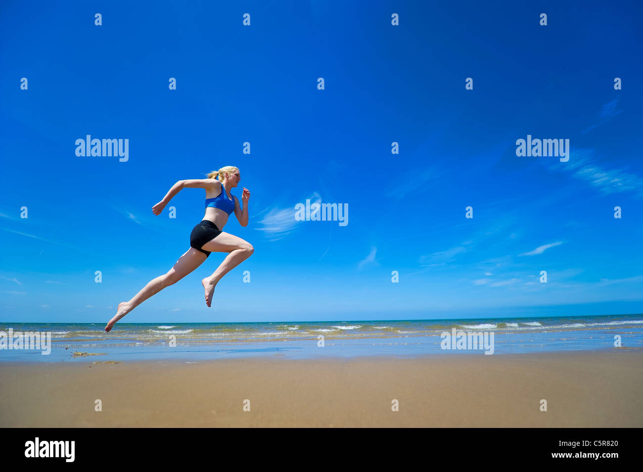 An athlete jogging along the oceans edge. - Stock Image