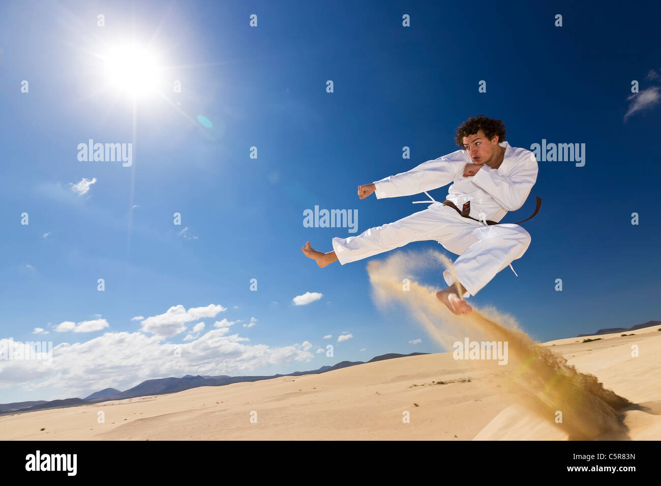 Martial artist training on dunes. - Stock Image