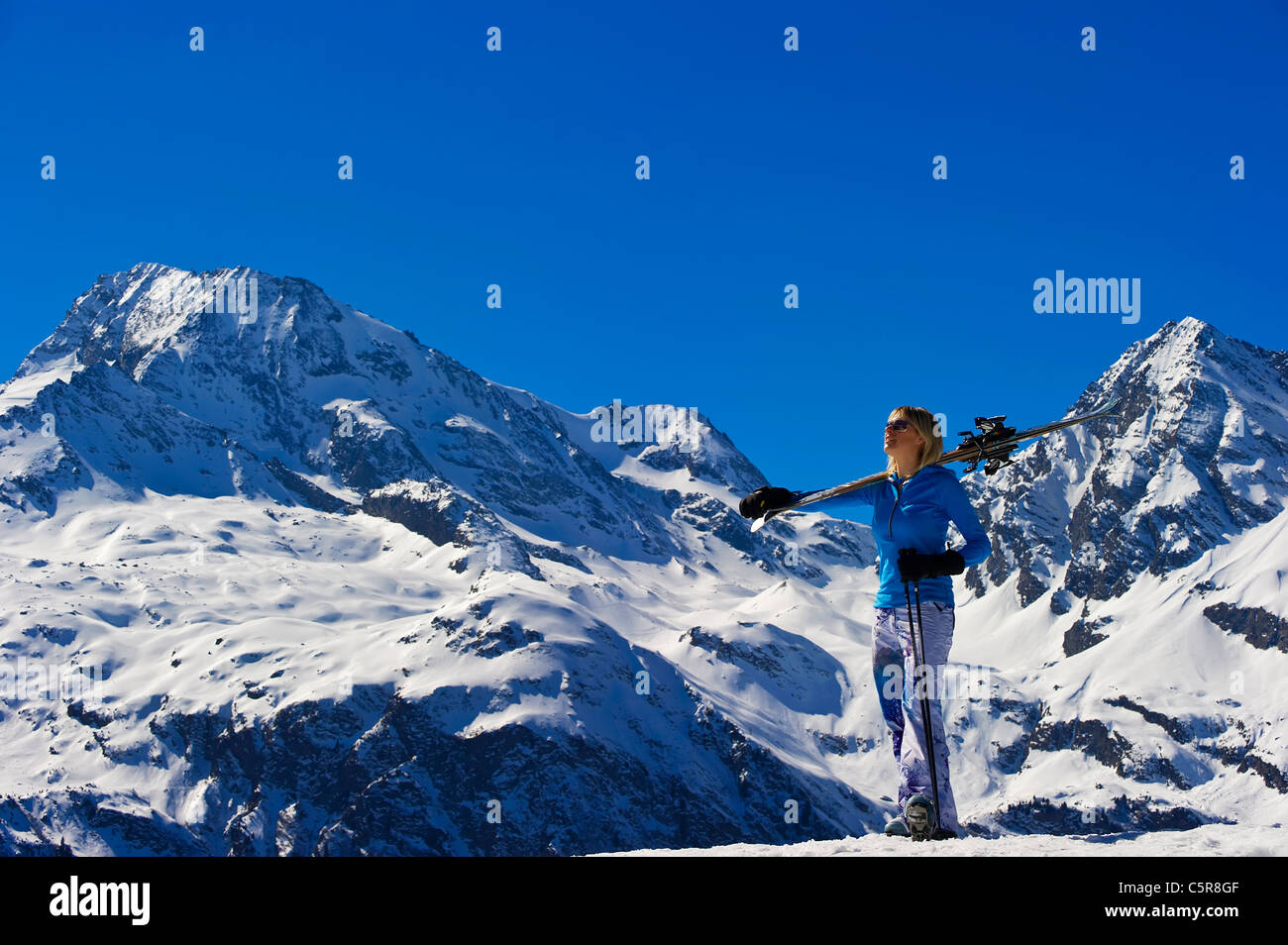 A women takes in the breathtaking snowy mountain view. - Stock Image