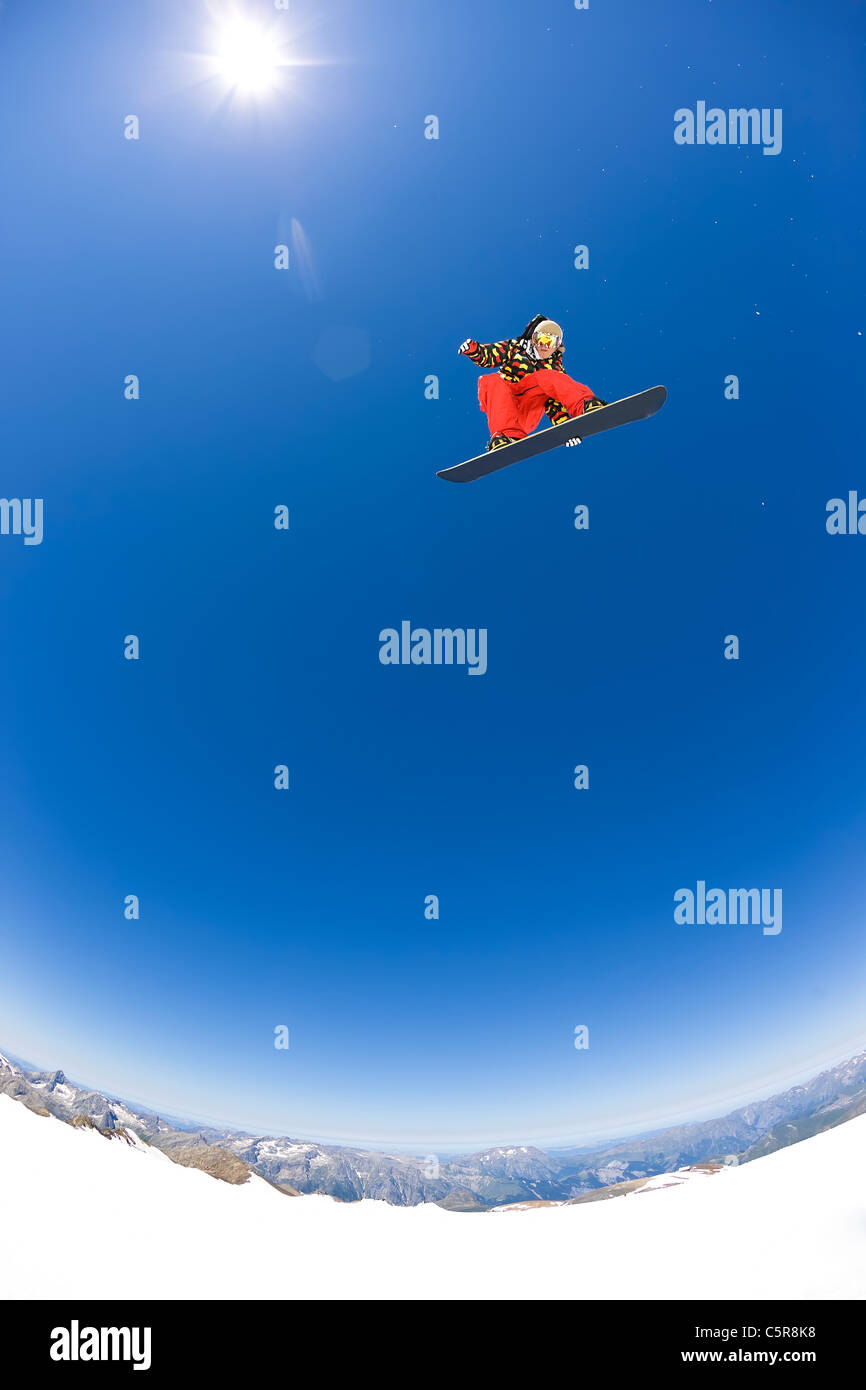 A Snowboarder flying high above the mountains and glaciers in the sun. - Stock Image