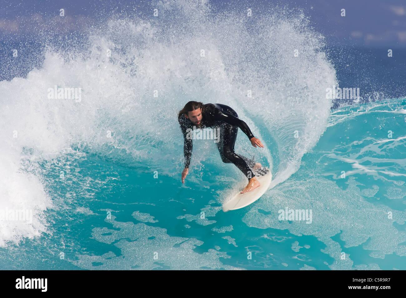 Surfer rides along azure blue wave. - Stock Image