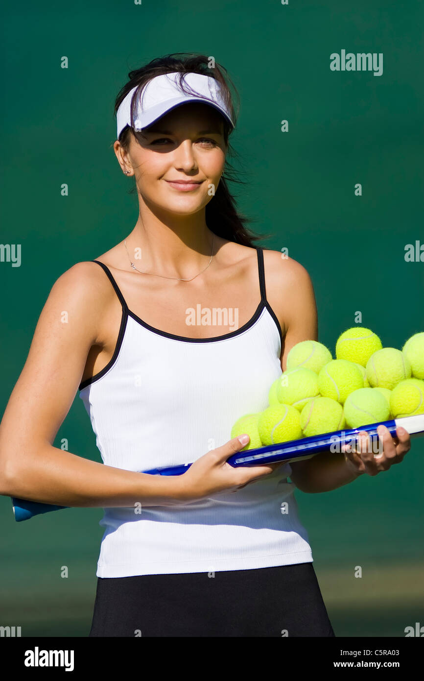 A tennis coach portrait with raquet and balls. - Stock Image