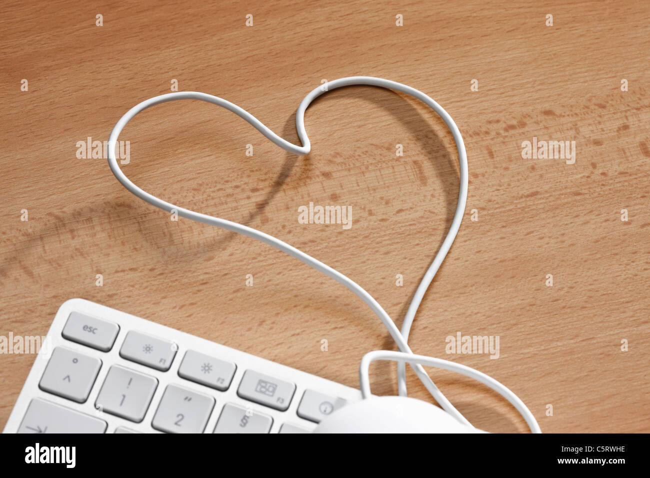 Computer keyboard with heart-shape wire, elevated view - Stock Image
