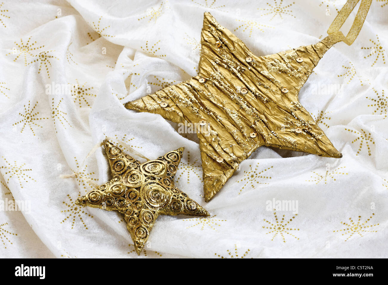 Christmas decoration, golden stars on tablecloth - Stock Image