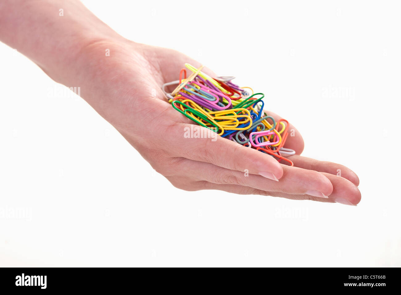 Close up of woman's hand holding paper clips against white background - Stock Image