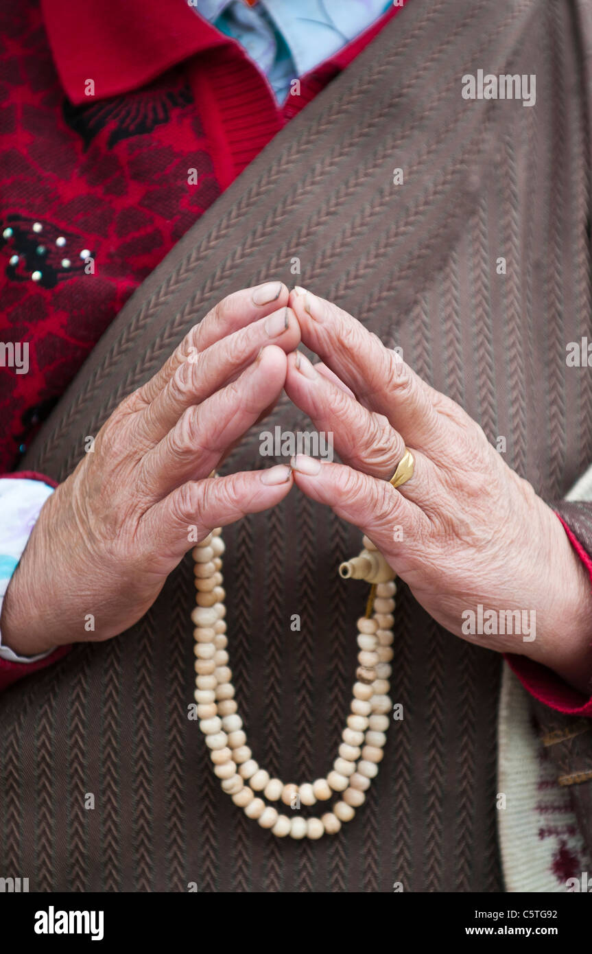 Elderly pilgrim with prayer beads, Kumbum Monastery, Huangzhong, Qinghai Province, China - Stock Image