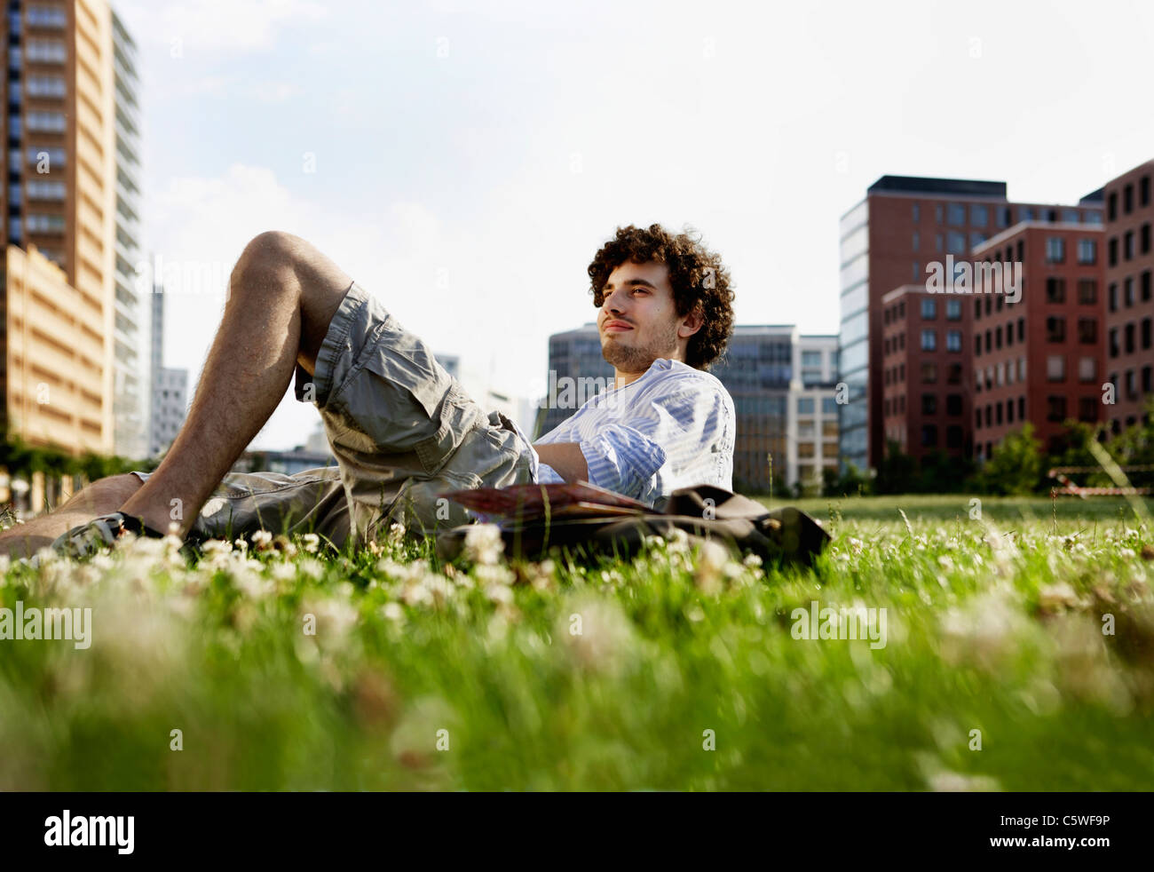 Germany, Berlin, Man relaxing on lawn, in background high rise buildings - Stock Image