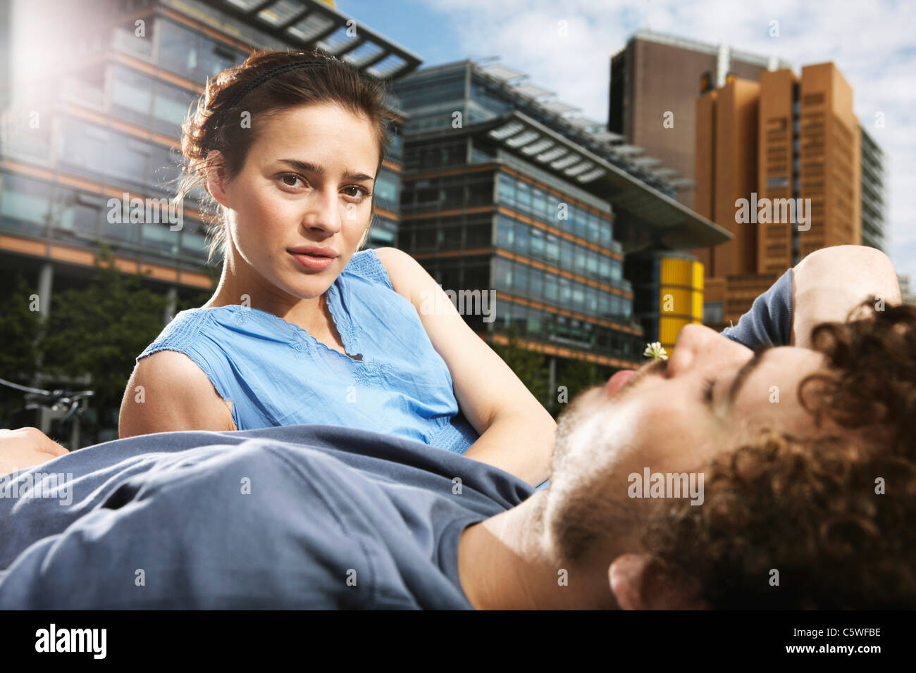 Germany, Berlin, Young couple lying in meadow, high rise buildings in background - Stock Image