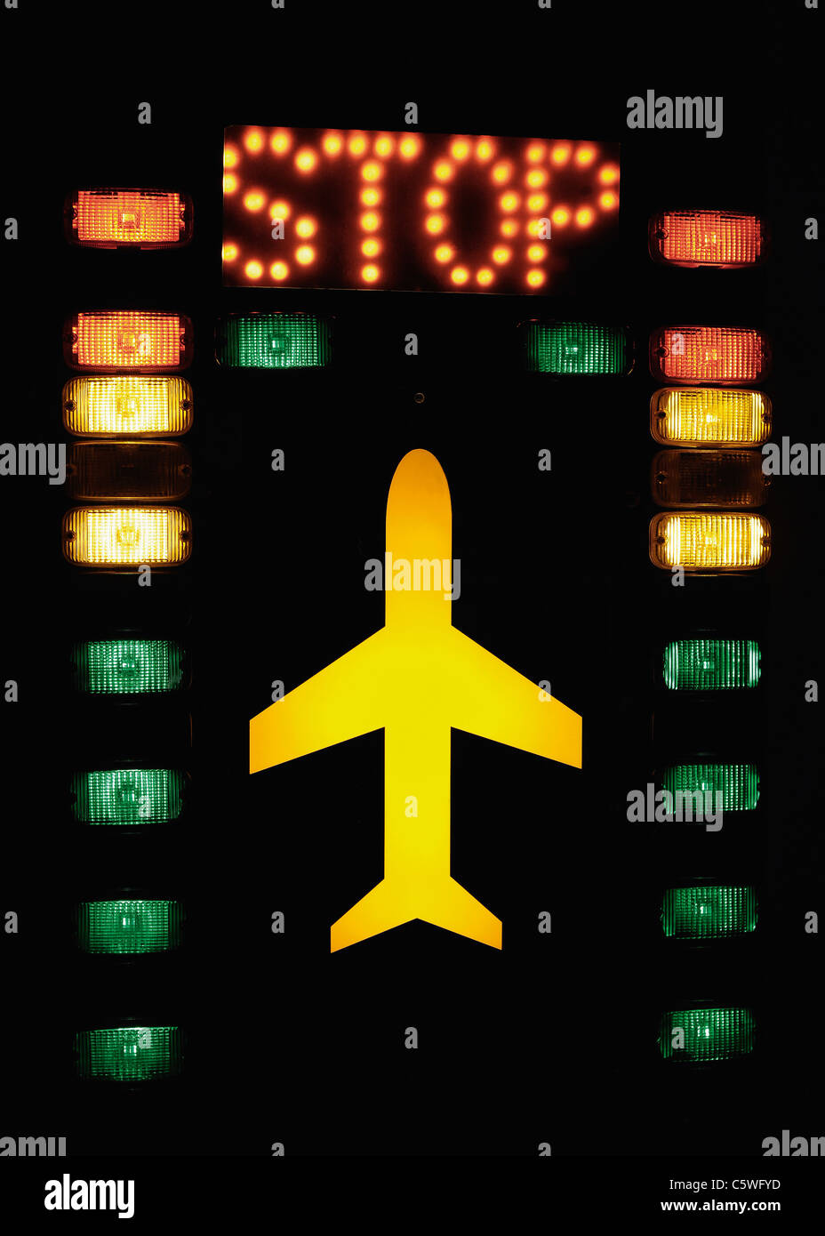 Germany, Lights with aircraft and stop sign on tower in airport - Stock Image
