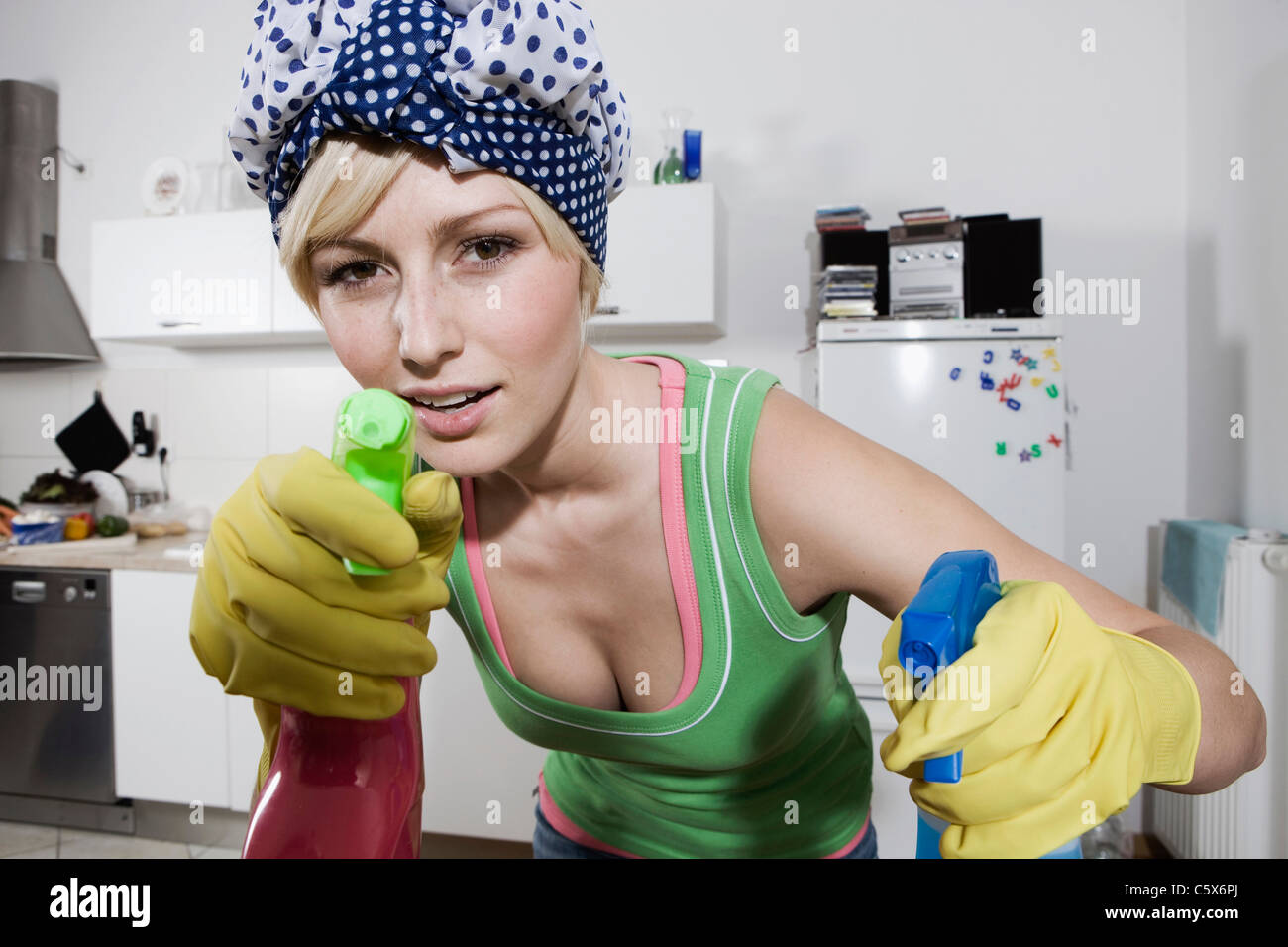Germany, Berlin, Young woman in kitchen holding spray bottles, portrait, close-up - Stock Image