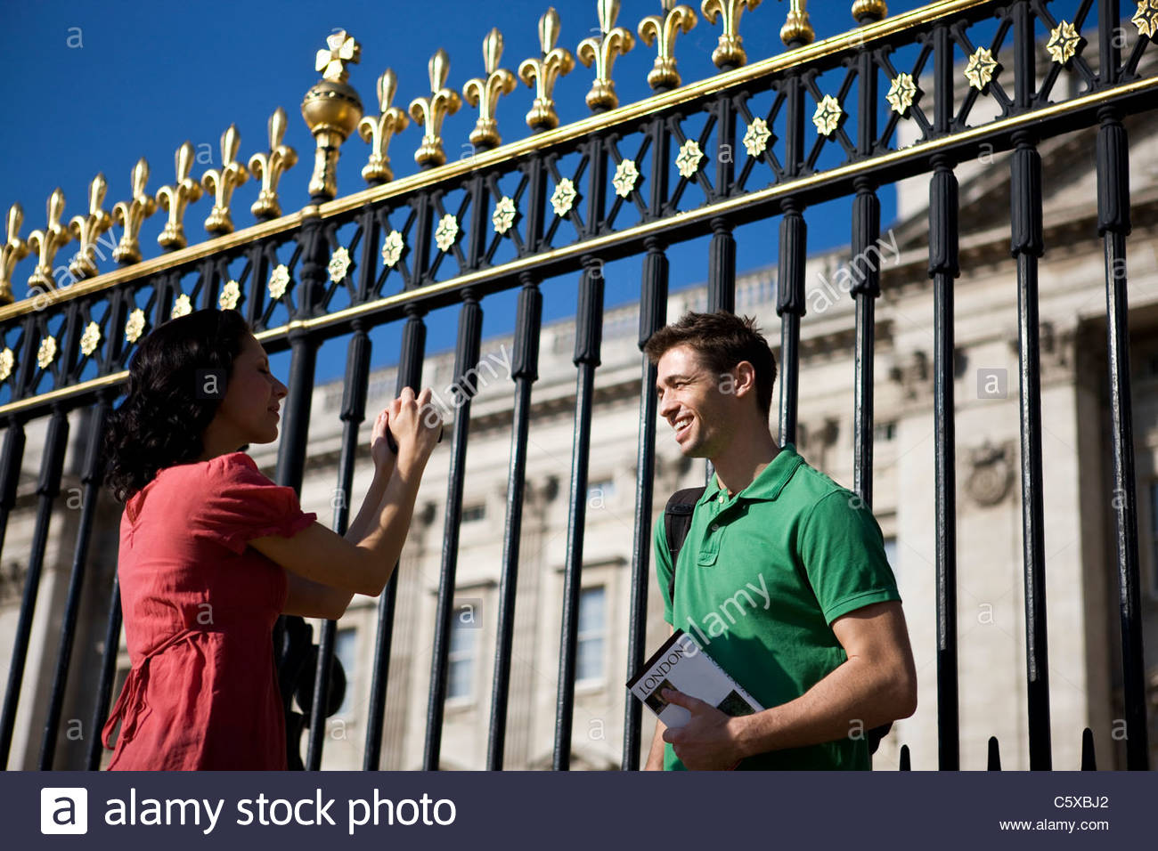 A young woman taking a picture of her boyfriend, in front of Buckingham Palace - Stock Image