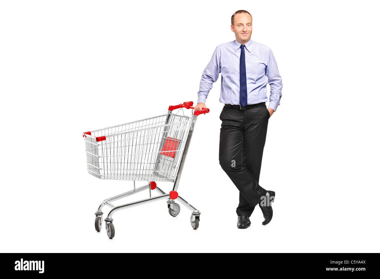 Full length portrait of a man posing next to an empty shopping cart - Stock Image