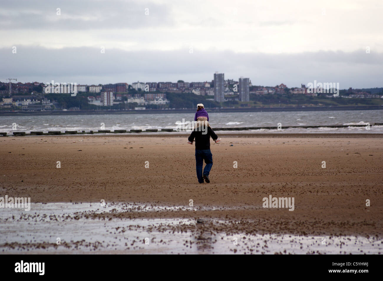 a-man-with-a-child-on-his-shoulders-crosby-beach-with-birkenhead-in-C5YHWJ.jpg