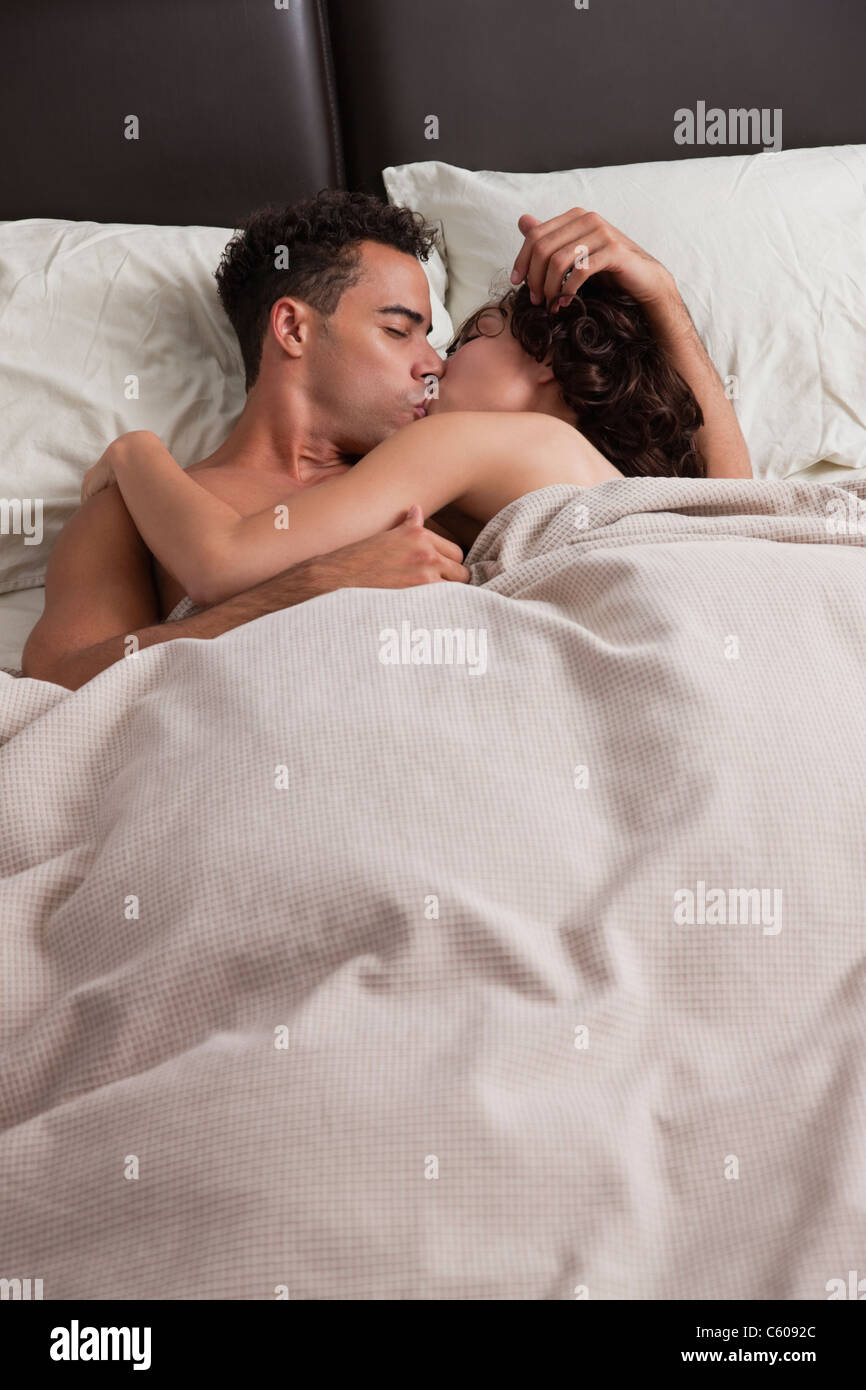 USA, New York City, Couple Kissing In Bed