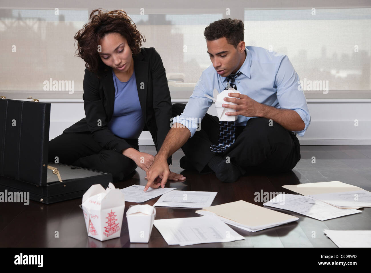 USA, New York City, businesspeople sitting on floor, discussing documents and eating Chinese take out food - Stock Image