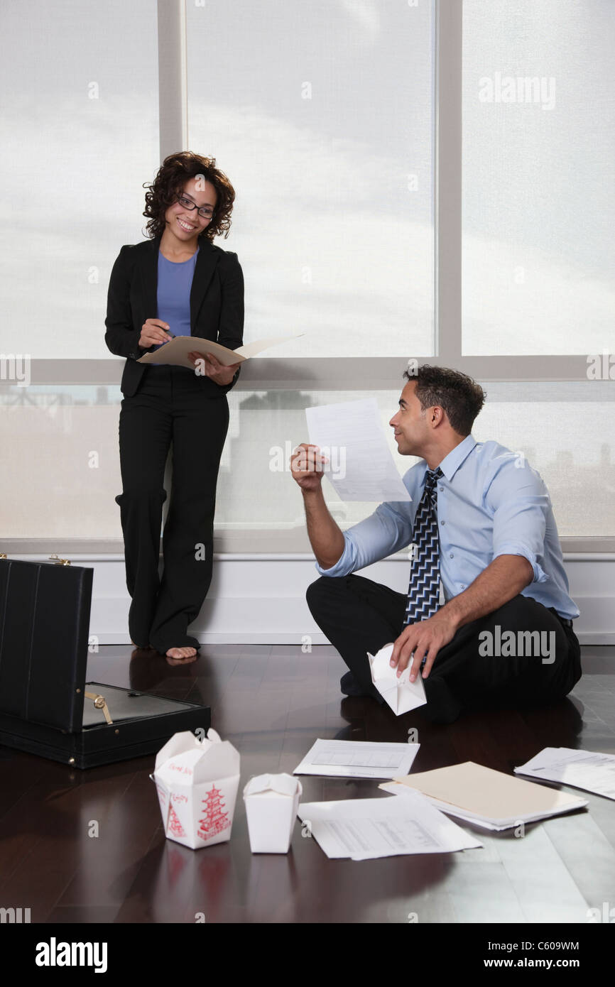USA, New York, New York City, businesspeople having meeting in hotel room, discussing documents and eating Chinese - Stock Image