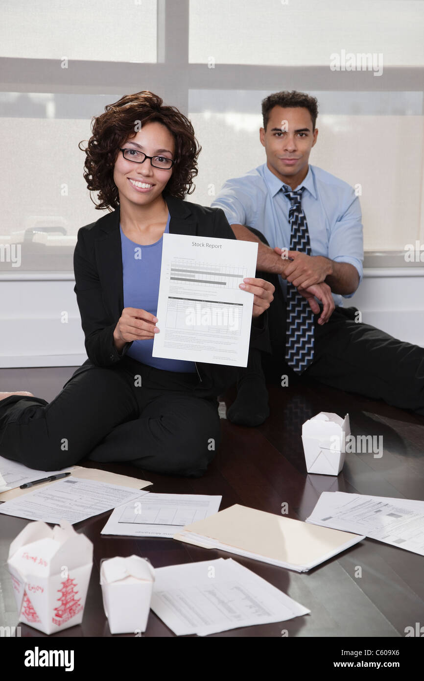 USA, New York, New York City, portrait of businesspeople sitting on floor in hotel room with documents - Stock Image