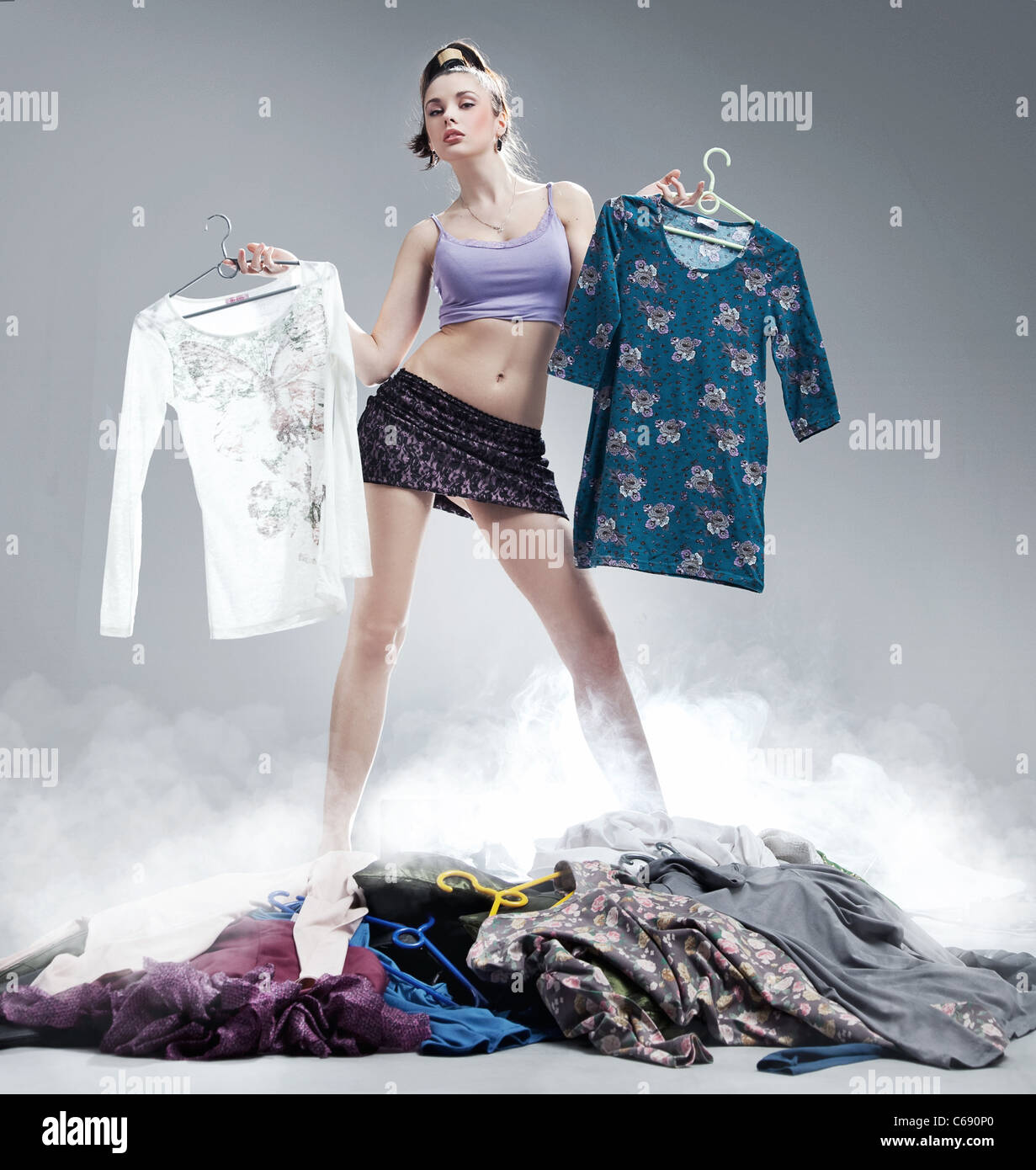 Young beautiful girl with many clothes - Stock Image