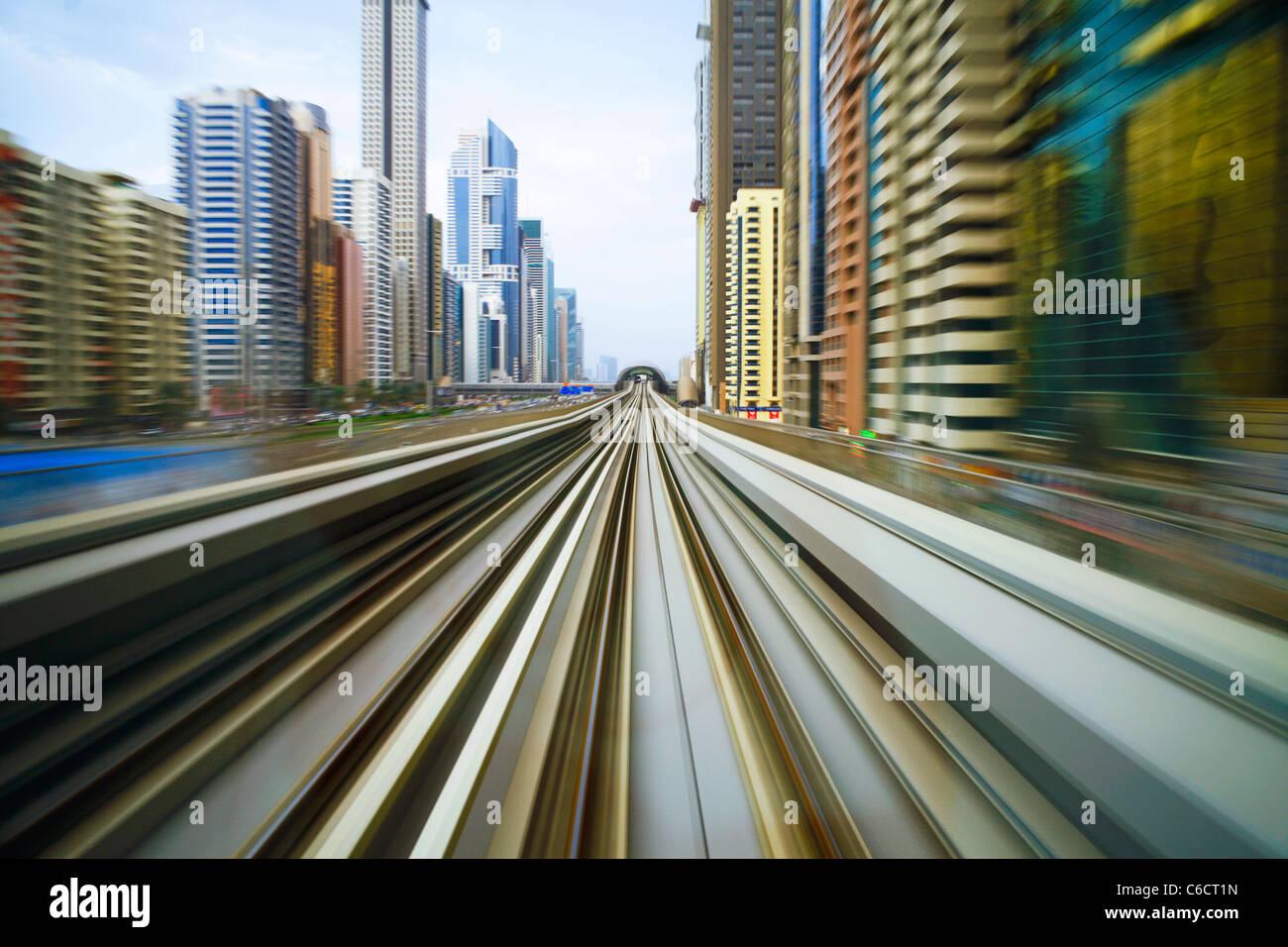 Opened in 2010, the Dubai Metro, MRT, in motion along Sheikh Zayed Road at dusk, Dubai, United Arab Emirates - Stock Image