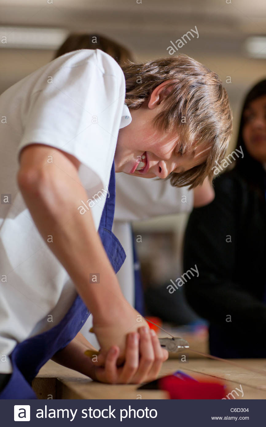 Boy using pliers to cut wire in school workshop - Stock Image