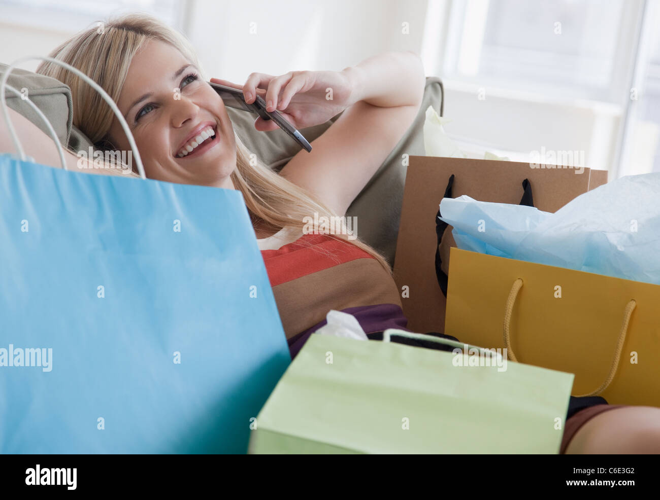 USA, New Jersey, Jersey City, Young woman talking on mobile phone surrounded by shopping bags - Stock Image