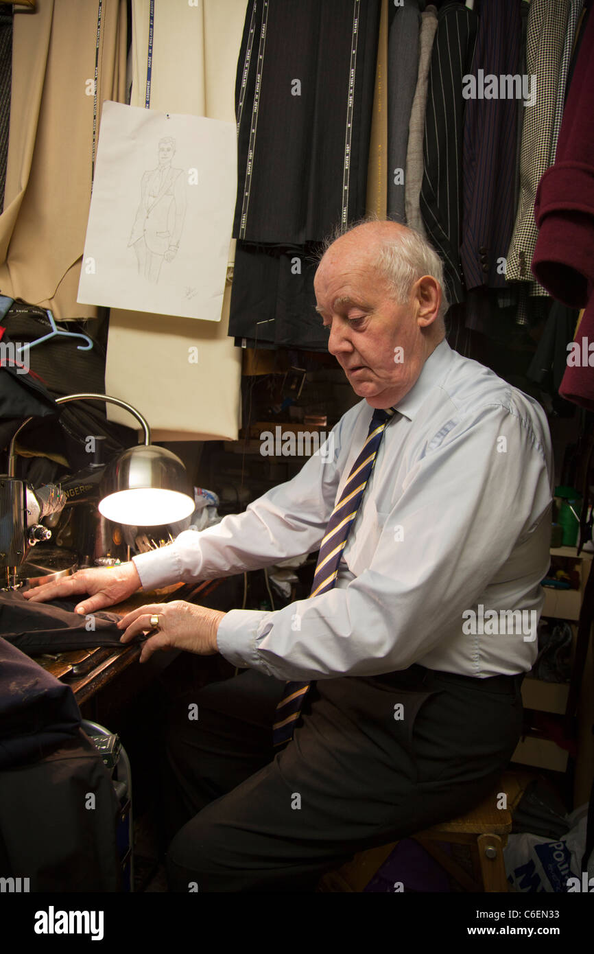 Tailor stitching a suit at work on his singer sewing machine old man working to make ends meet tailoring - Stock Image